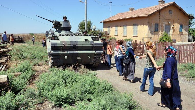 Een vredesdemonstratie, begin augustus, in de Turkse grensplaats Mardin, waar dit weekeinde twee Nederlanders werden opgepakt. Turkse soldaten kijken toe vanuit een pantservoertuig. Beeld afp