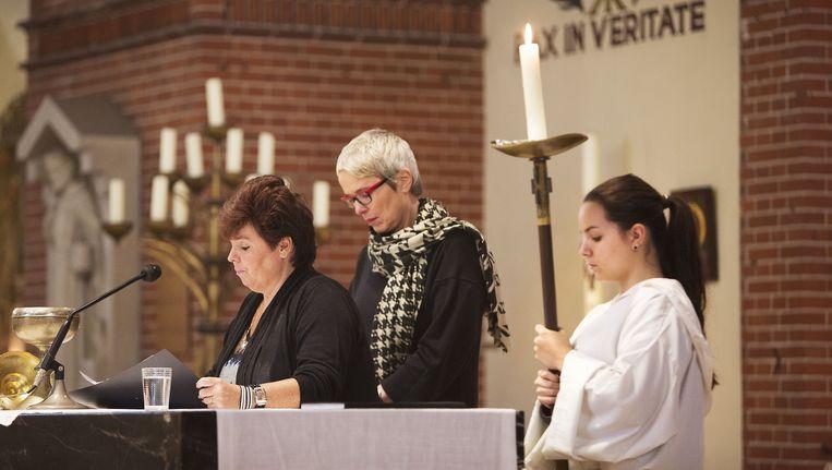 Pia Wagenaar (midden) gaat voor in de eucharistieviering, bijgestaan door Lydia van den Heuvel en haar dochter Mandy. Beeld Werry Crone