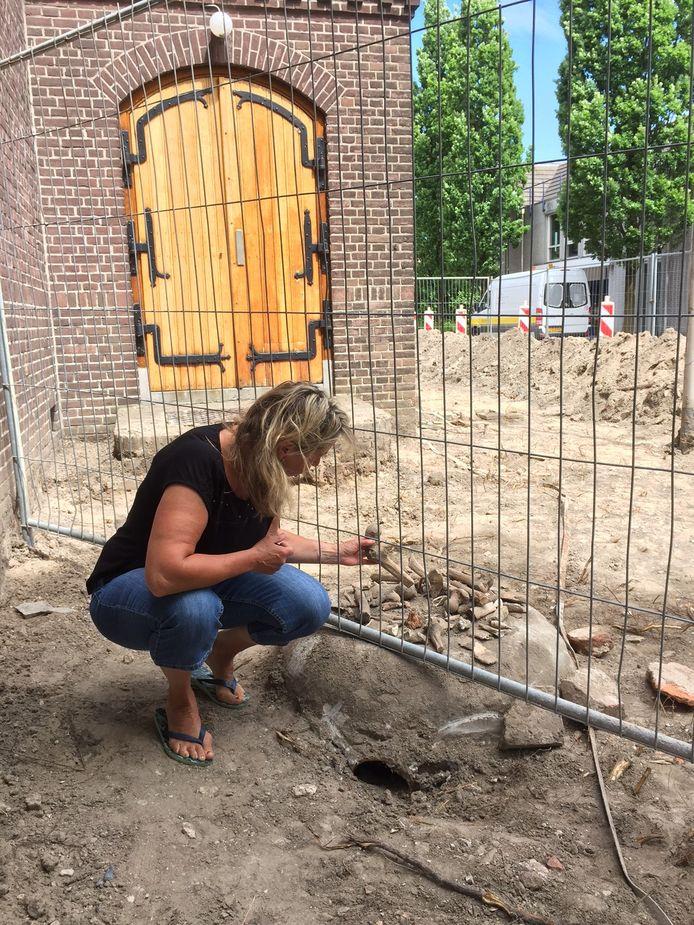 Gerda Oskam inspecteert enkele menselijke botten bij de Marekerk in De Meern.