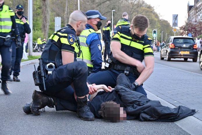 De politie arresteert een bezoeker van het 'festival' in het Arnhemse park Sonsbeek die niet vrijwillig het park wilde verlaten.