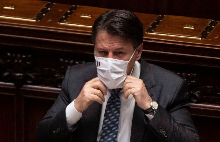 De Italiaanse premier Conte doet zijn mondmasker weer op na een speech over het coronavirus in het Italiaanse parlement. Beeld EPA