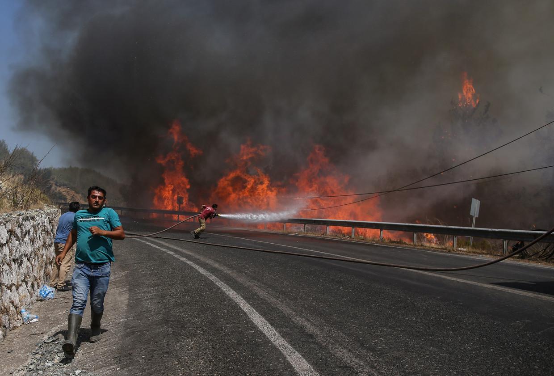 Brandweerlui proberen de vlammen te doven in de badplaats Marmaris in Turkije.  Acht mensen kwamen al om het leven in het land, enkele honderden anderen raakten gewond en duizenden omwonenden moesten geëvacueerd worden Beeld EPA