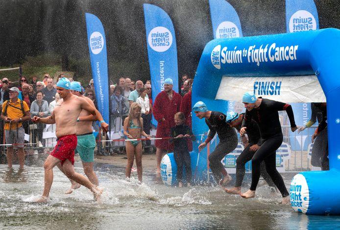 Deelnemers stormen het water van Stroombroek in.