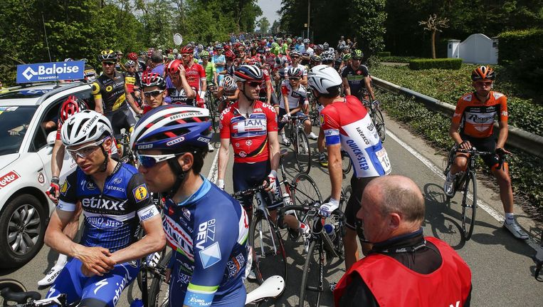 Renners wachten vertwijfeld op nieuws nadat de derde rit van de Ronde van België in Verviers is stilgelegd. Beeld © Jan De Meuleneir / Photonews