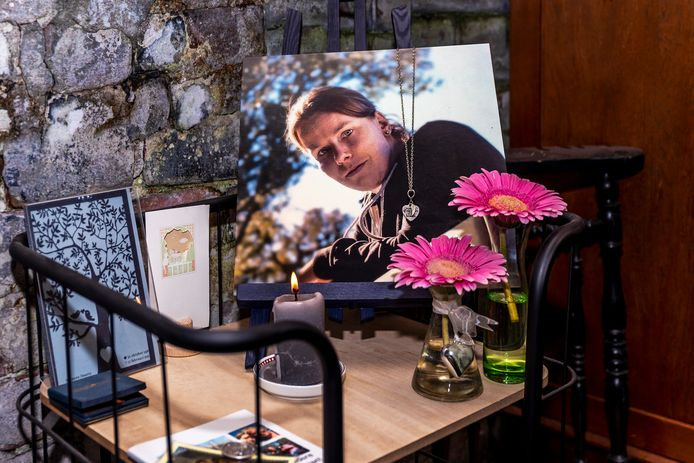 Bloemen en een kaars bij een foto ter herinnering aan Suzanne.