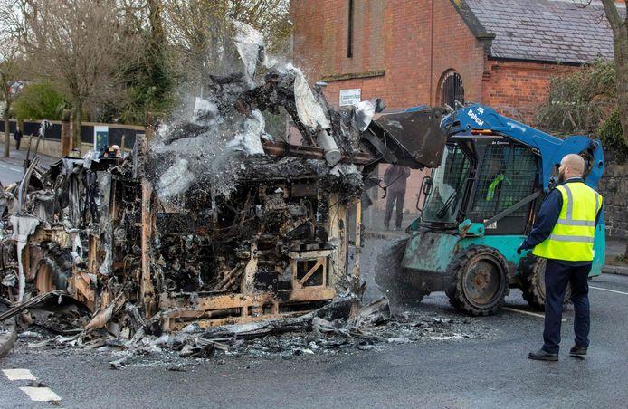 Een ambtenaar in Belfast neemt de schade op nadat loyalisten op de beruchte Shankill Road een bus in brand hebben gestoken.