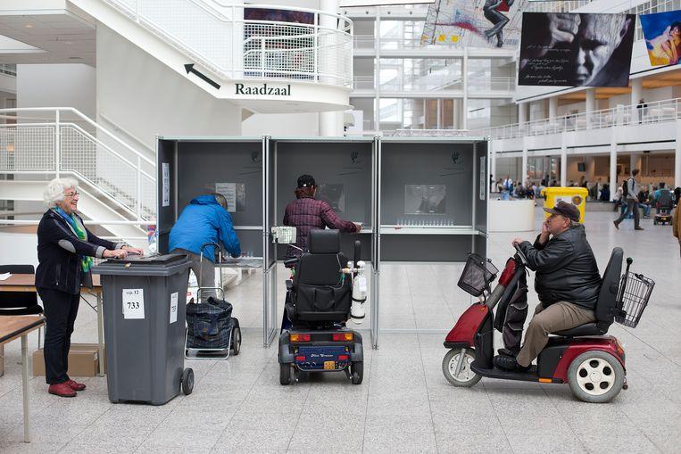 Een stemhokje in het Atrium in Den Haag bij de Tweede Kamerverkiezingen van 2012. Vooral laagopgeleide jongeren weten het stemhokje moeilijk te vinden.  Beeld  ANP