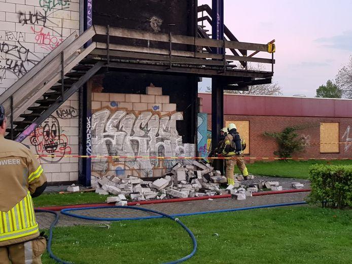 De brandweer hakt de muur onder de brandhaard nog verder weg.