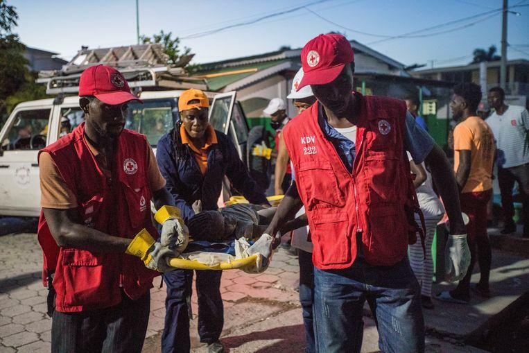 Medewerkers van het Rode Kruis vervoeren een jong slachtoffer van de aardbeving.  Beeld REUTERS