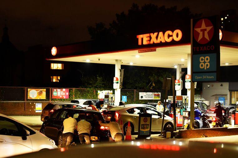 Mensen duwen een auto die geen brandstof meer heeft de laatste meters naar de pomp in Londen.   Beeld Reuters