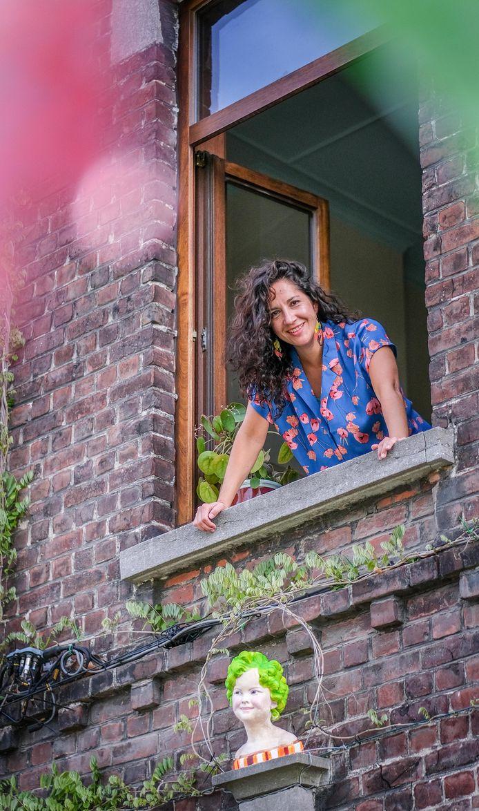 Mónica kijkt uit het raam op de eerste verdieping. Onder haar een beschilderd beeldje van Hollywood-ster Shirley Temple.