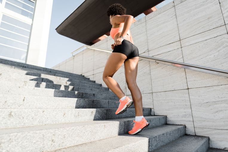 Running fit woman. Woman runner training outdoors on staircase. Beeld Getty Images