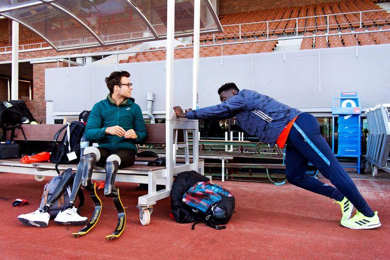 Flip Breuer en Elvis Afrifa tijdens een training van Team Para Atletiek in het Olympisch Stadion. Beeld Olaf Kraak