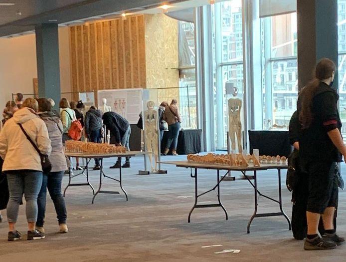 Une exposition faite de bric et de broc, avec des tables pliantes en plastique, dans un cadre austère.