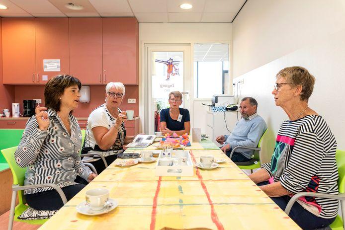 Vrijwilligers (links en midden) en bezoekers (rechts) gezellig aan de koffie bij de eerste keer 'Onder Mekaore' in Kruisland.