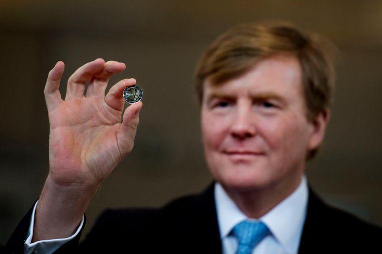 De koning in 2014 tijdens de presentatie van de door Erwin Olaf ontworpen 2 euro-munt met daarop zijn beeltenis. Beeld anp