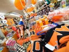 Oranje vlaggetjes vlogen over de toonbank; klanten vissen achter het net