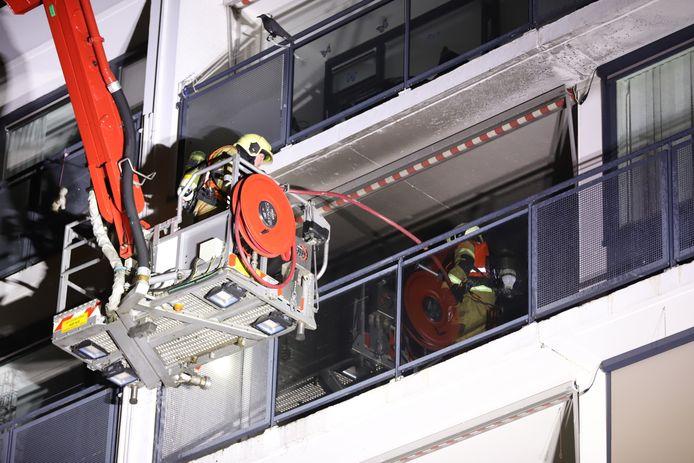 Brandweer blust op het balkon van het appartementencomplex in Veghel.