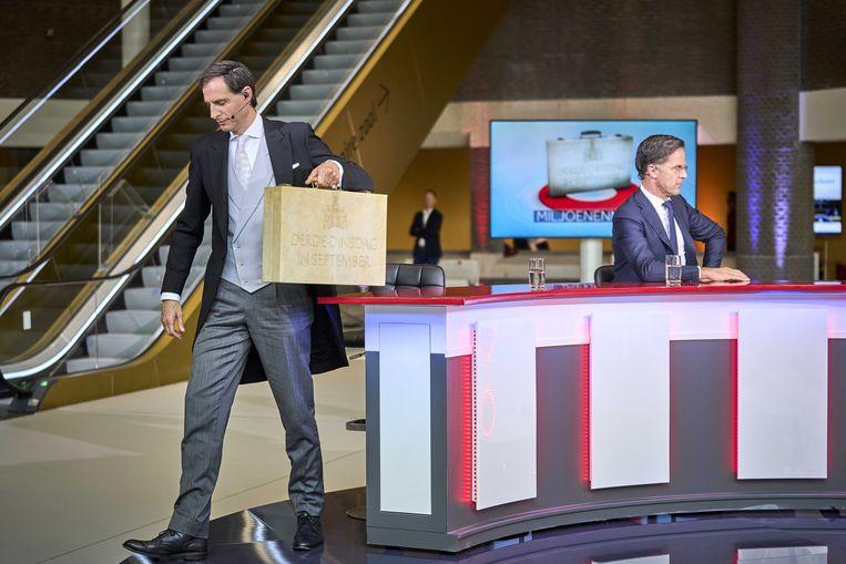 Demissionair minister Hoekstra (Financien) met 'het koffertje', en zittend achter hem demissionair premier Rutte, na de presentatie van de rijksbegroting en de miljoenennota in de Tweede Kamer. Beeld ANP
