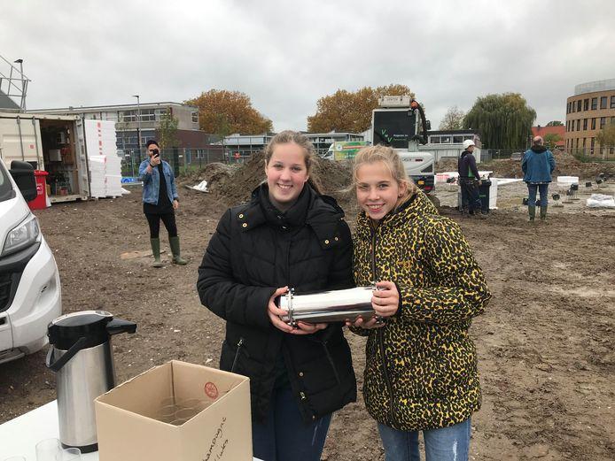 Denise (links) en Lonneke van praktijkschool De Brug met de tijdcapsule, waarin informatie over hun school anno 2020 zit.