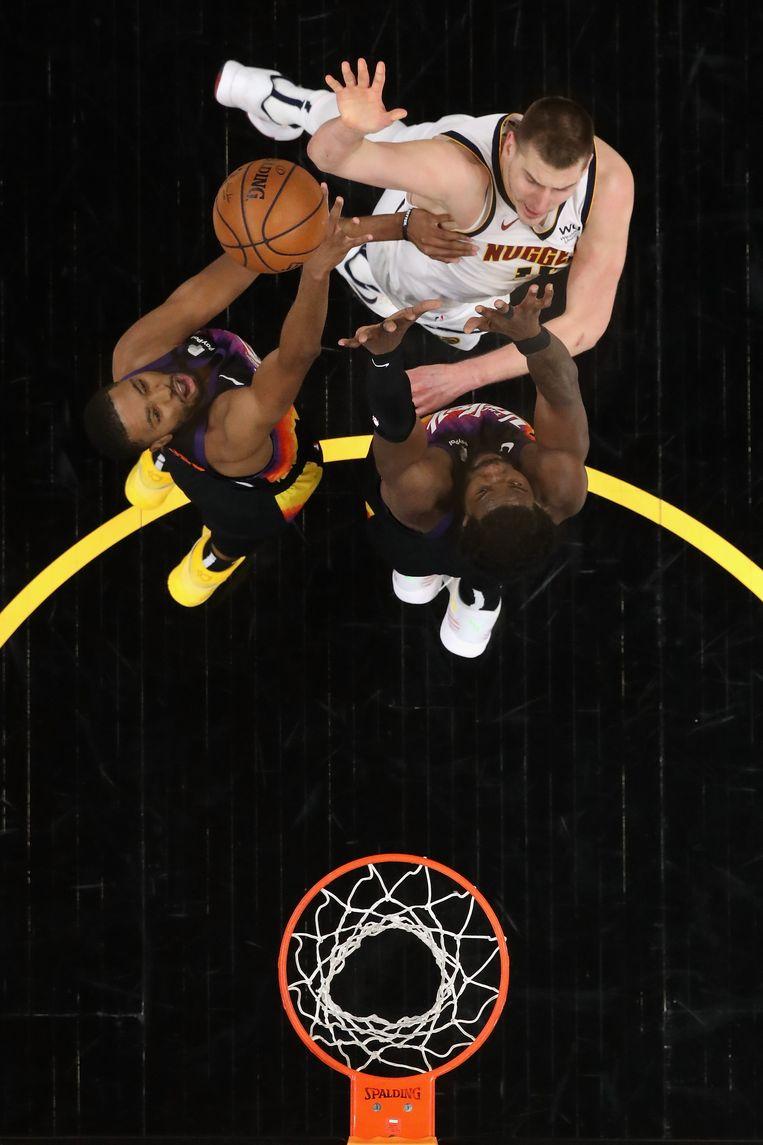 Jokic speelt de bal over Mikal Bridges en Deandre Ayton van Phoenix Suns naar de basket van de Suns, 7 juni, 2021. Beeld AFP