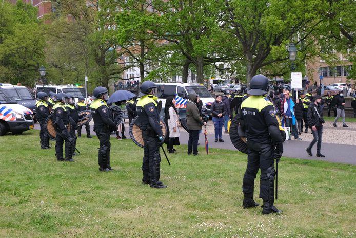 Agenten met helm en schild staan op het Malieveld in Den Haag.