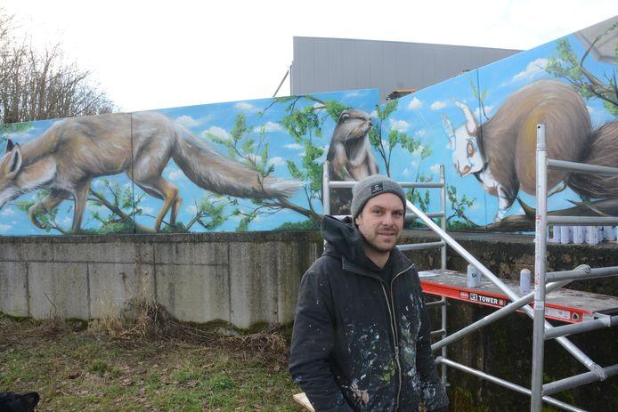 David is bezig met de laatste afwerkingen van de graffitimuur.