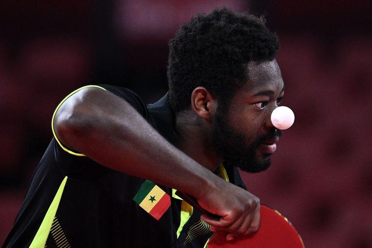 Ibrahima Diaw kijkt de bal na bij zijn opslag tijdens het olympisch tafeltennistoernooi in het hoofdstedelijk gymnasium vanTokio. De speler uit Senegal stond in de eerste ronde tegenover Clarence Chew uit Singepore. Chew won.  Beeld AFP