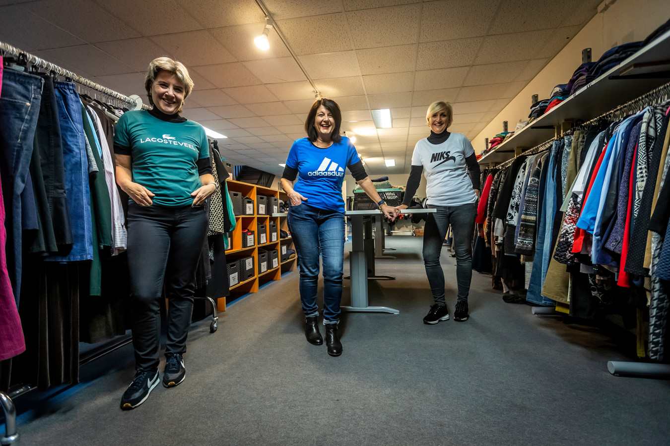De Kledingbank in Eindhoven komt met een parodiërende kledinglijn van bekende merken. (Vlnr) Medewerksters Emily, Marja en Wendy.