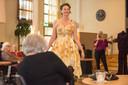 Medewerkster Fleur van De Wilgenhof is even model voor een jurk van Agnes van Dijk (op de achtergrond) tijdens de modeshow in het verzorgingshuis.