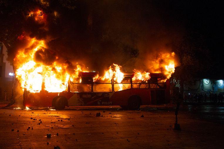 Een bus werd in brand gestoken door de demonstranten. Beeld AFP