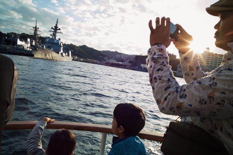 Toeristen vergapen zich aan een oorlogsschip in Yokosuka in Japan.  Beeld Kentaro Takahashi