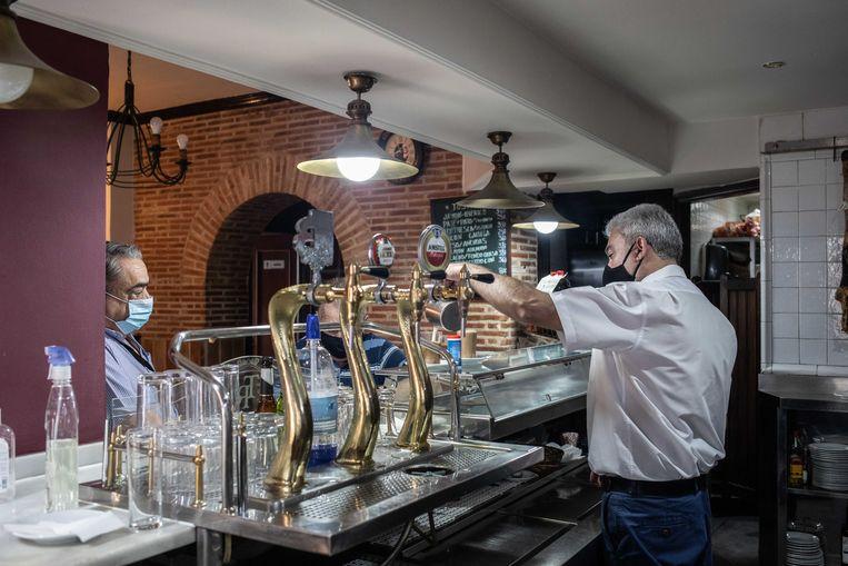 Door kleine ondernemers zoals hij komt het in elk geval níet dat het virus in Madrid weer de kop opsteekt, zegt bareigenaar Antonio Camacho. Beeld César Dezfuli