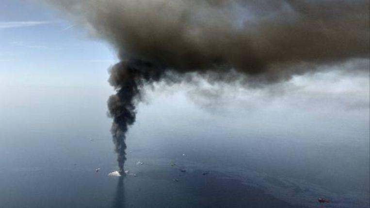 Een luchtfoto van de Golf van Mexico met het brandende boorplatform en de olievlek. (AP) Beeld