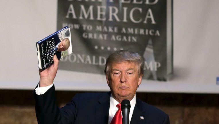 Donald Trump met zijn nieuwe boek 'Crippled America' in de aanslag. Beeld REUTERS