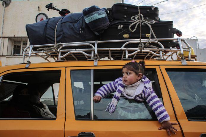 Een meisje kijkt uit het raam van een auto terwijl ze wacht aan de grensovergang tussen de Gazastrook en Egypte. Archiefbeeld.