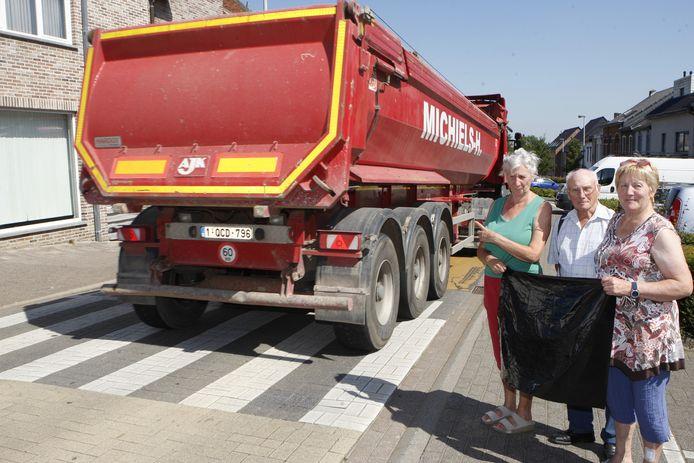 Marie Stevens (l.) met de familie Clygnet in de straat, terwijl een vrachtwagen langsrijdt.