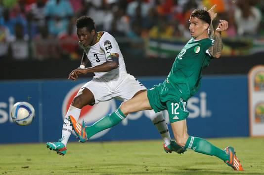 Asamoah Gyan (links) 'vliegt' voorbij de Algerijn Carl Medjani.