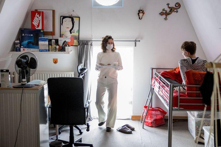 Een gezin in quarantaine: zoon krijgt zijn eten op zijn kamer. Beeld Arie Kievit