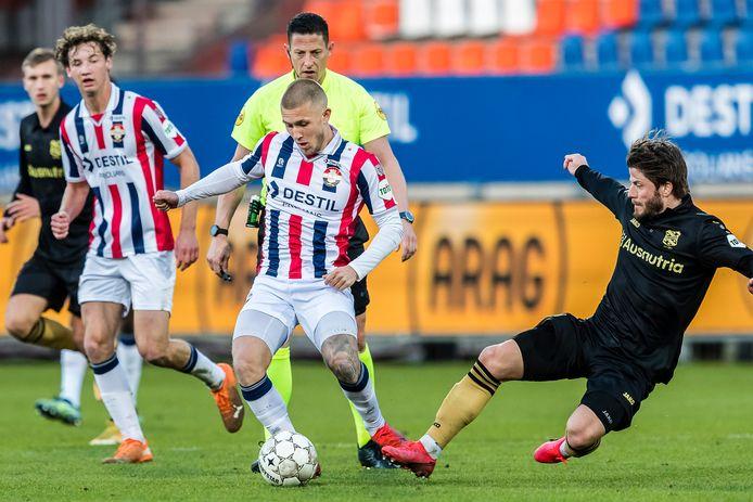 Ian Smeulers (midden) speelt de bal weg tijdens de thuiswedstrijd tegen SC Heerenveen; de tackle van Lasse Schöne komt te laat. Links kijkt Wesley Spieringhs toe.