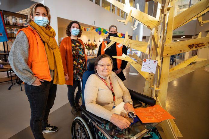 Gineke Roggen, bewoonster van Archipel Landrijt hangt als eerste een wenskaart in de boom. Links achter haar Judith Helderman, intermediair bij Samen voor Eindhoven.