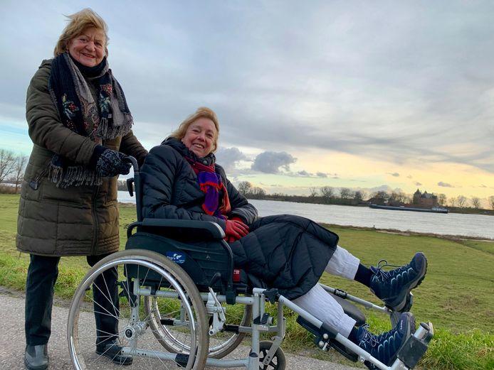 Sjoukje van der Burgh (l) en Ria Willemstein wandelen over de Waaldijk. Ria zit in een rolstoel omdat ze een nieuwe knie heeft en de revalidatie niet zo lekker gaat.