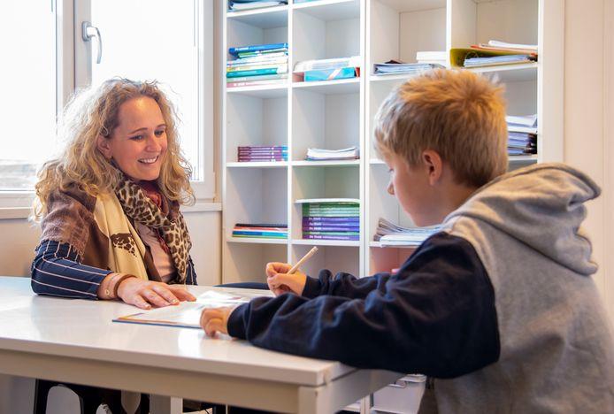 Jantine van Hunenstijn van JAM Harderwijk geeft bijles aan Jens. Deze zomer krijgen kinderen die in armoede leven gratis bijlessen, dankzij financiering door Stichting Leergeld Randmeren.