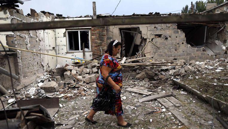 Een vrouw loopt langs een vernield huis in Donetsk, Oekraïne. Een Russisch konvooi is onderweg, maar of ze haar zullen helpen? Beeld afp
