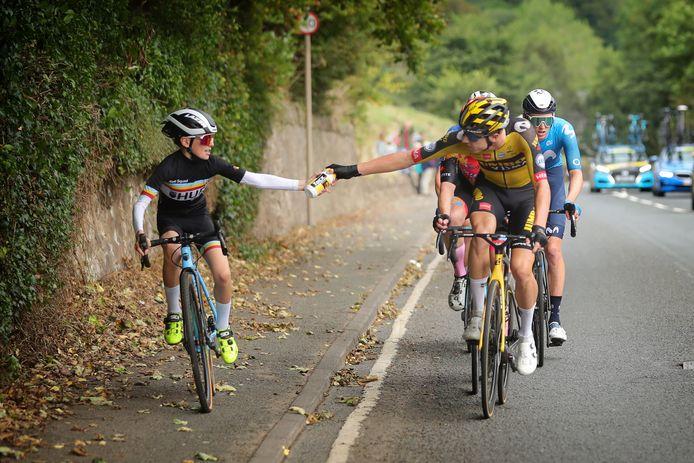 Pascal Eenkhoorn geeft de bidon aan de jonge renner.