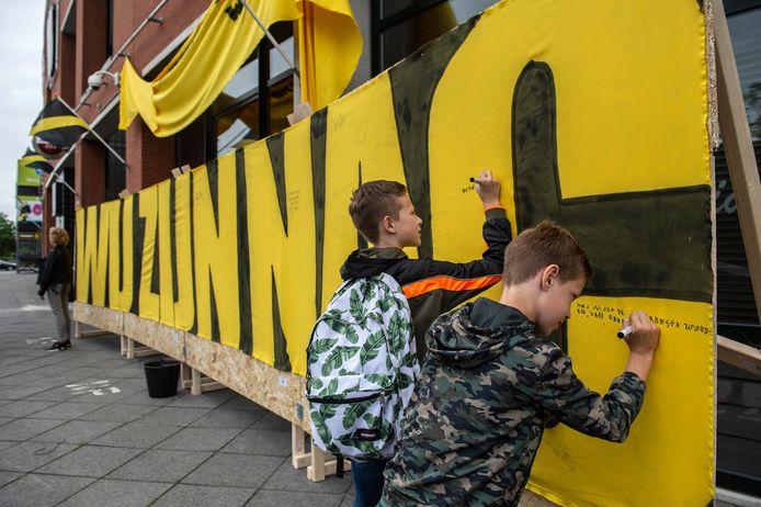 Juup (12 jaar, links) en Gijs  (8 jaar) laten een wens achter op de wensmuur. 'NAC moet de allerbeste worden van de eredivisie'.