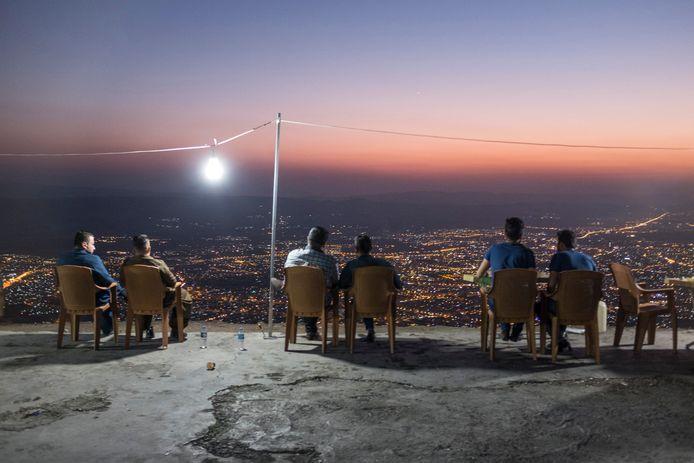 In Irak kijken mannen bij het vallen van de avond vanaf de berg Azmir uit over Soeleimania. Boven op de berg is een plek waar de oorlog ver weg lijkt.