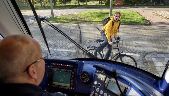 Met een hoofdtelefoon op verzonken in gedachten op de fiets springen, levert geregeld problemen voor bestuurders van de Haagse HTM.