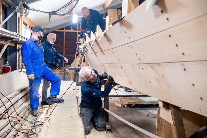 Scheepstimmerman Harmen Timmerman  (r)  was dinsdagochtend met twee vrijwilligers aan het werk in de Ommer scheepswerf.