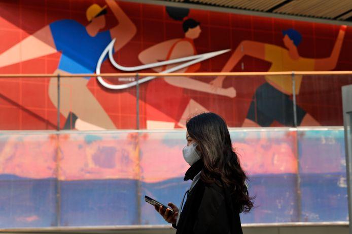 Een vrouw wandelt voorbij een Nike-winkel in de Chinese hoofdstad Peking.